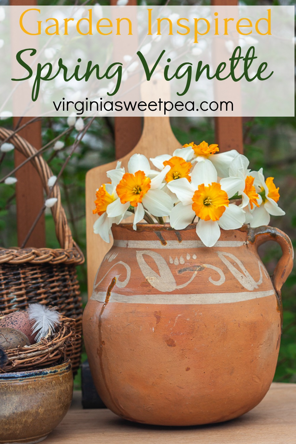 Spring vignette with an antique southerwestern pottery jug filled with daffodils, and antique basket, a pottery bowl holding a nest, and a wooden cutting board.