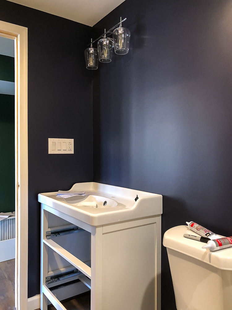 Toilet and Vanity installed in a bathroom painted with Sherwin Williams Charcoal Blue