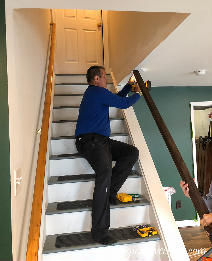 Screwing a banister to the ceiling on a staircase