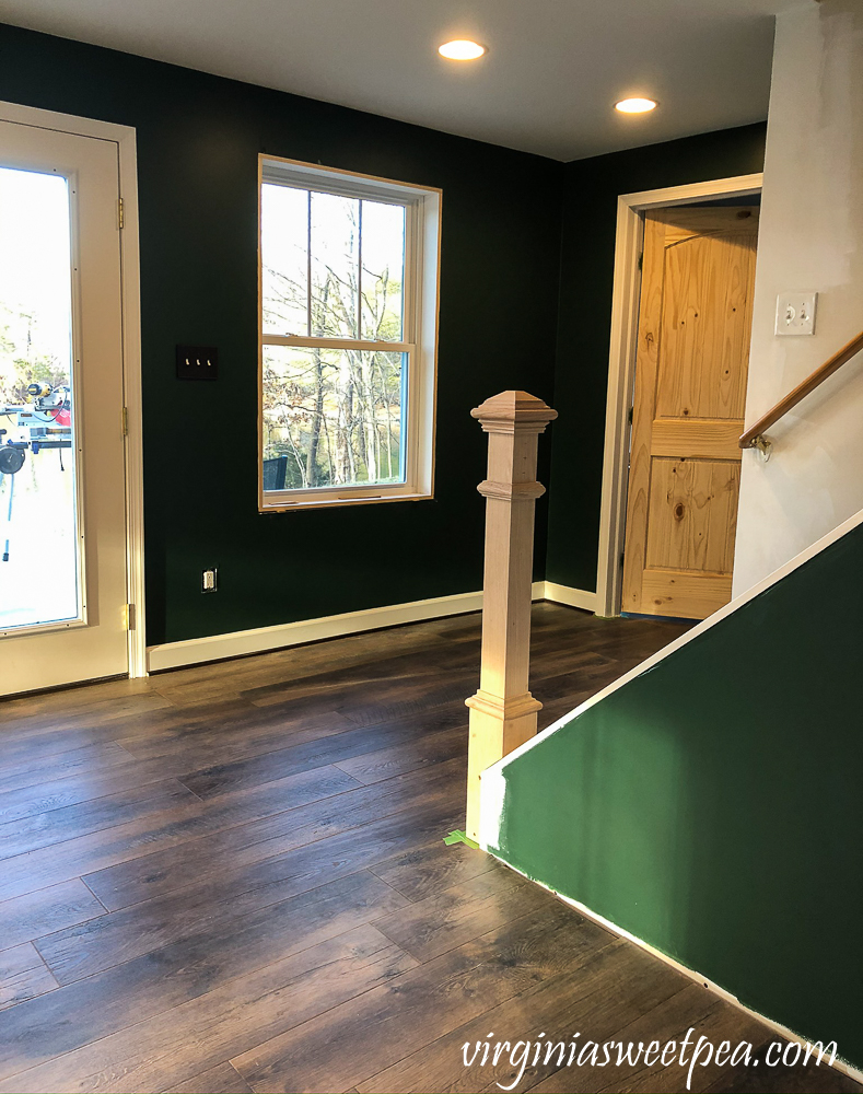 Newel post installed at the bottom of a set of stairs in a basement family room