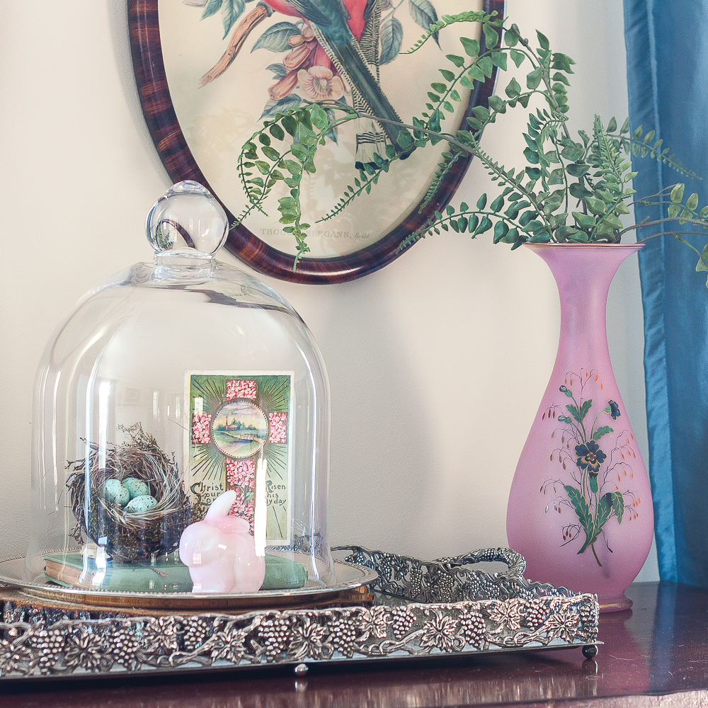 Spring Vignette with a cloche with nest, fenton rabbit and postcard, pink vase with faux ferns