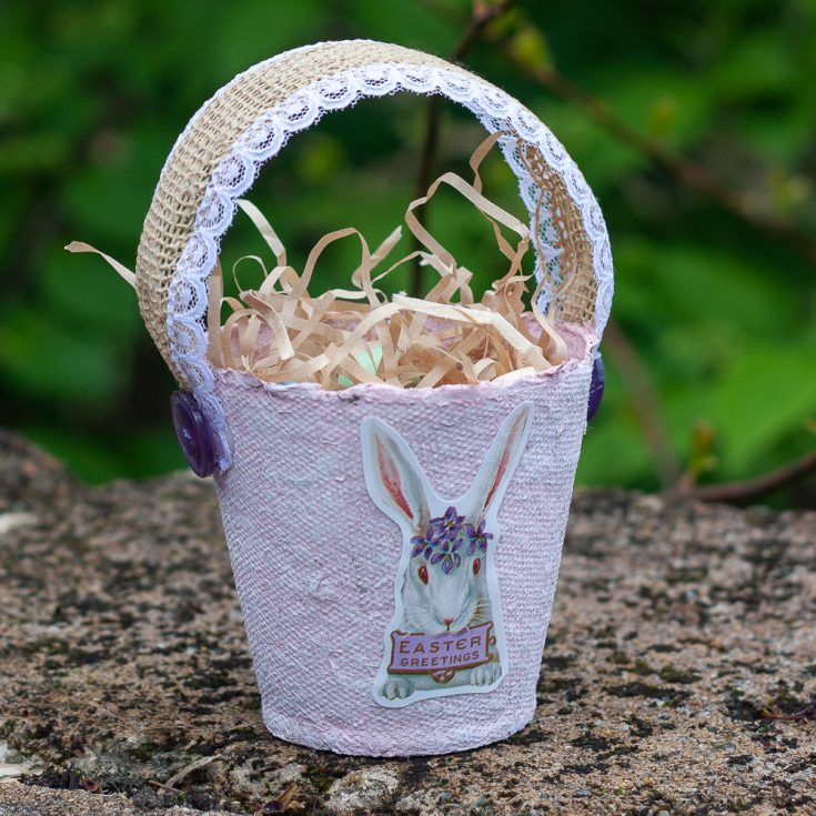 Easter treat basket made using a peat pot, ribbon, buttons, and an Easter sticker