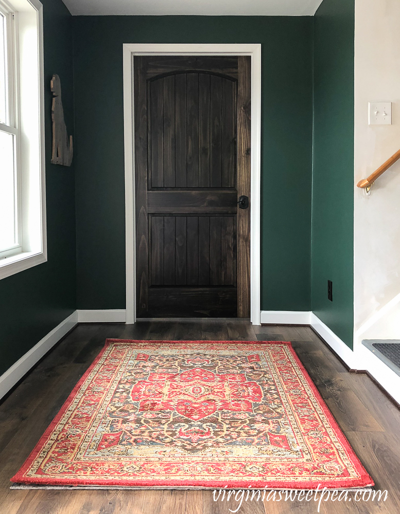 Walls painted with Sherwin Williams Emerald Paint in Rock Garden and dark stained wood door