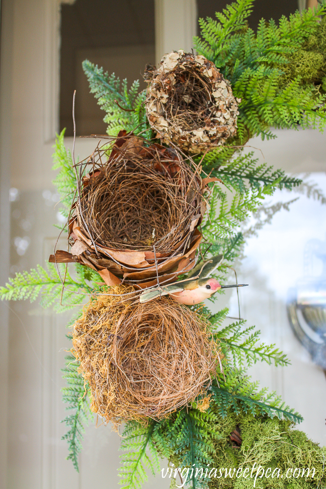 Three natural birds nests on a wreath with faux ferns and a faux hummingbird