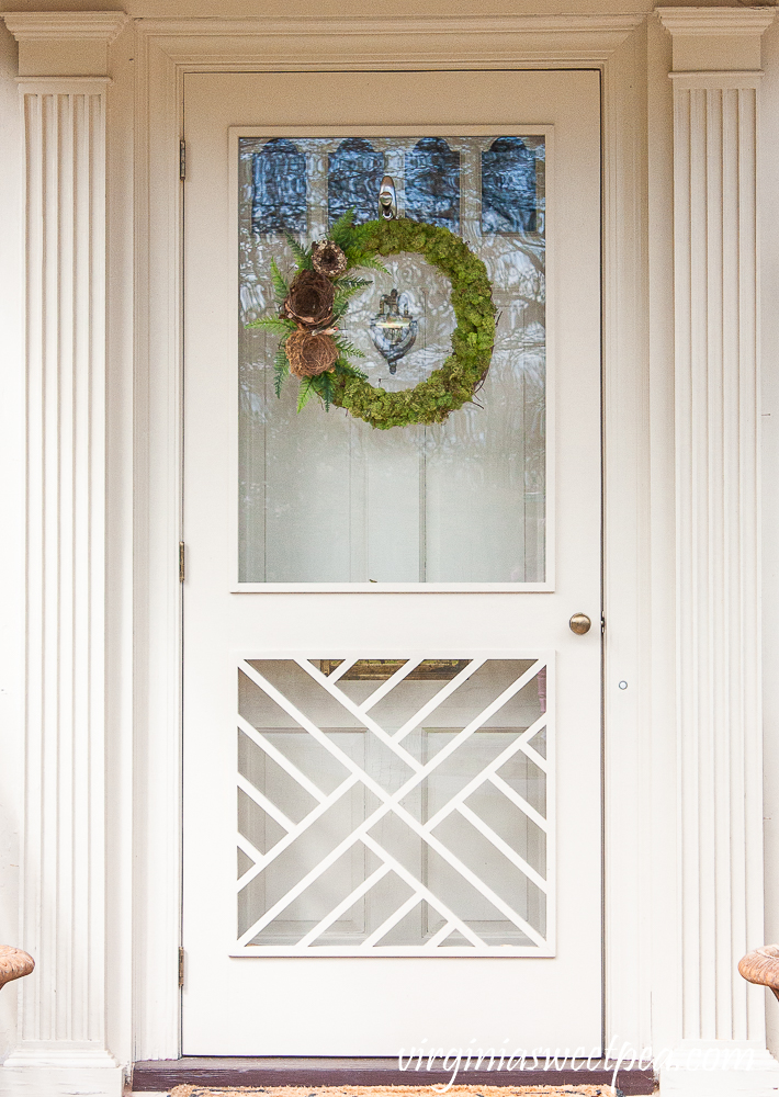 Chippendale door with a spring wreath covered in moss with birds nests and ferns on the side.