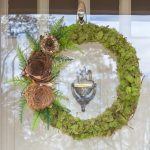Wreath covered in moss with three nests, ferns, and a hummingbird on the side.
