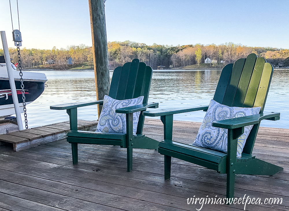 Two adirondack chairs on a dock with pillows