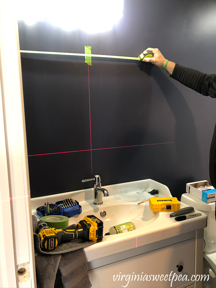Using a laser level to help install a mirror in a bathroom.