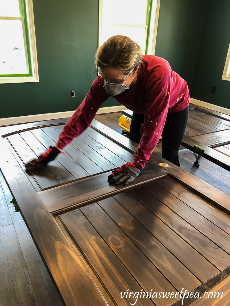 Finishing wood doors by staining and using steel wool between coats of topcoat.