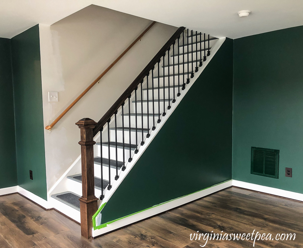 Staircase with metal balusters and wood banister and newel post.