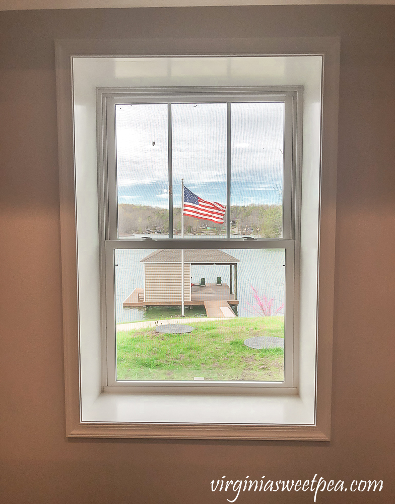 Framed window with American flag flying in the background.