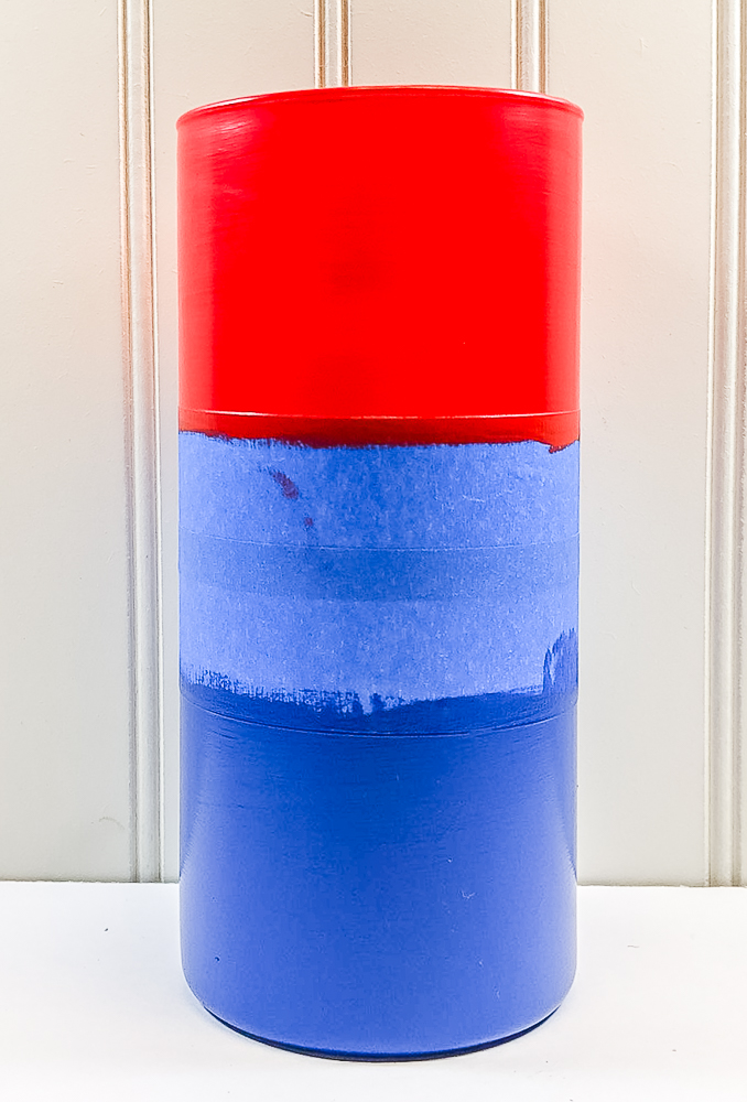 Vase painted red at the top and blue at the bottom with painter's tape in the middel