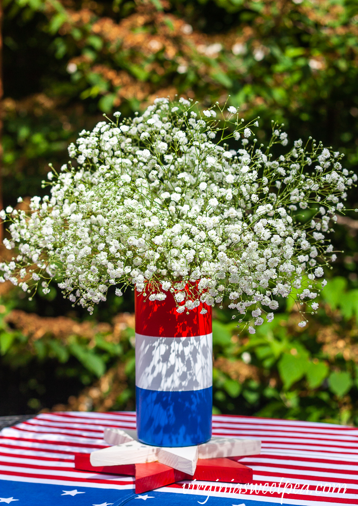 Red, white, and blue striped vase filled with Baby's Breath.