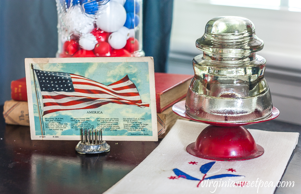 Vintage American flag postcard with a glass insulator on top of a red candle holder on a vintage towel