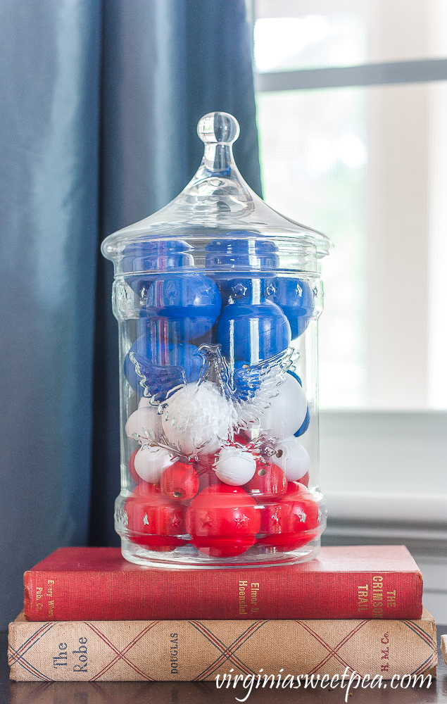 Patriotic Vignette with 1976 eagle jar with red, white, amd blue filler made from wood beads and ping-pong balls stacked on two vintage books