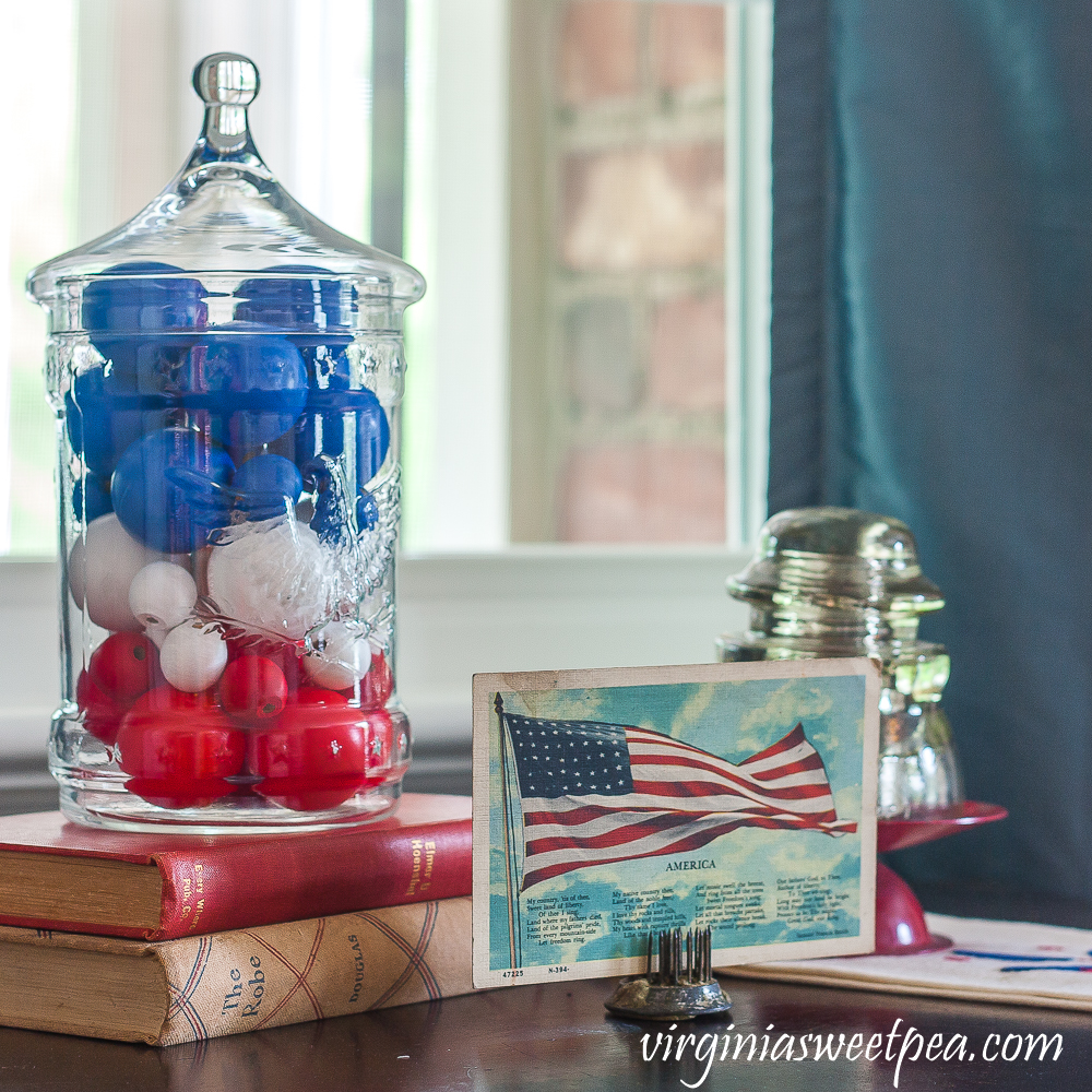 Patriotic Vignette with 1976 eagle jar with red, white, amd blue filler, American flag postcard, and glass insulator on a red candle stand on top of a vintage towel