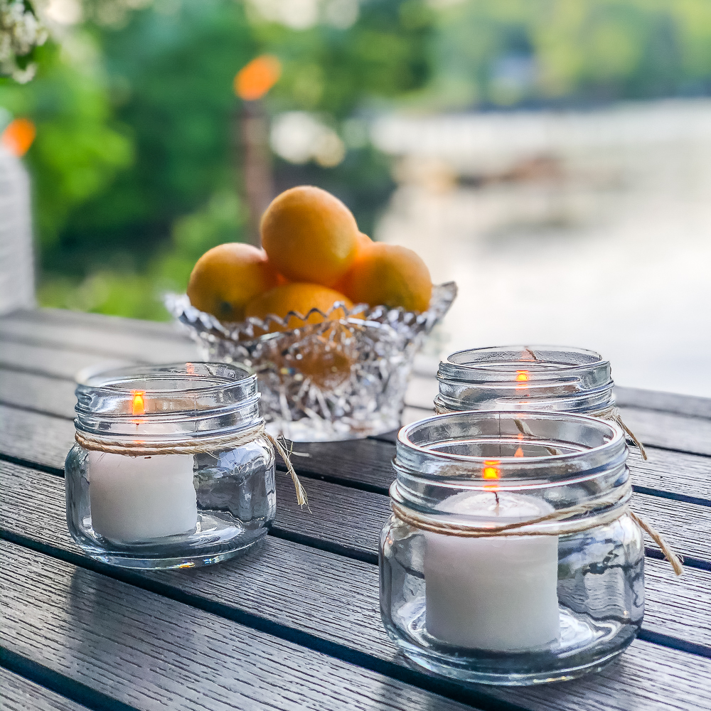 Candles in jars with twine tied around them and a bowl of lemons