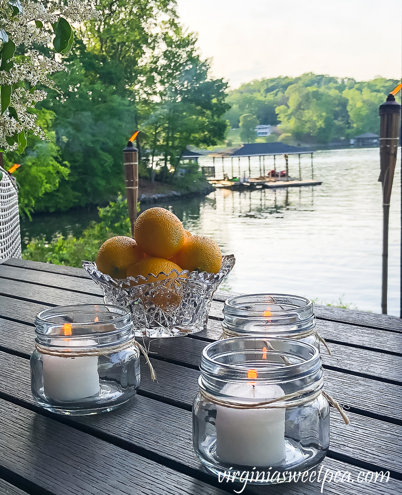 Citronella candles in Mason jars with a bowl of lemons all with a lake view