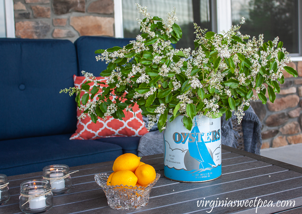 Flowers on a patio in a vintage oyster can with candles and a bowl of lemons
