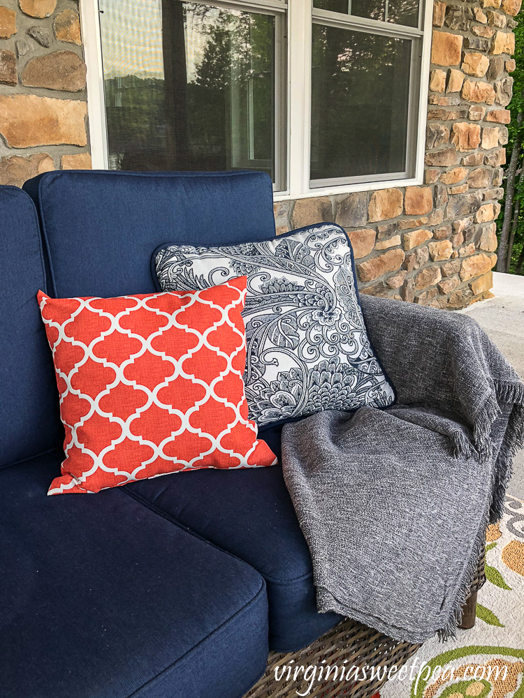 Pillows and a throw on a sofa on a lake house patio