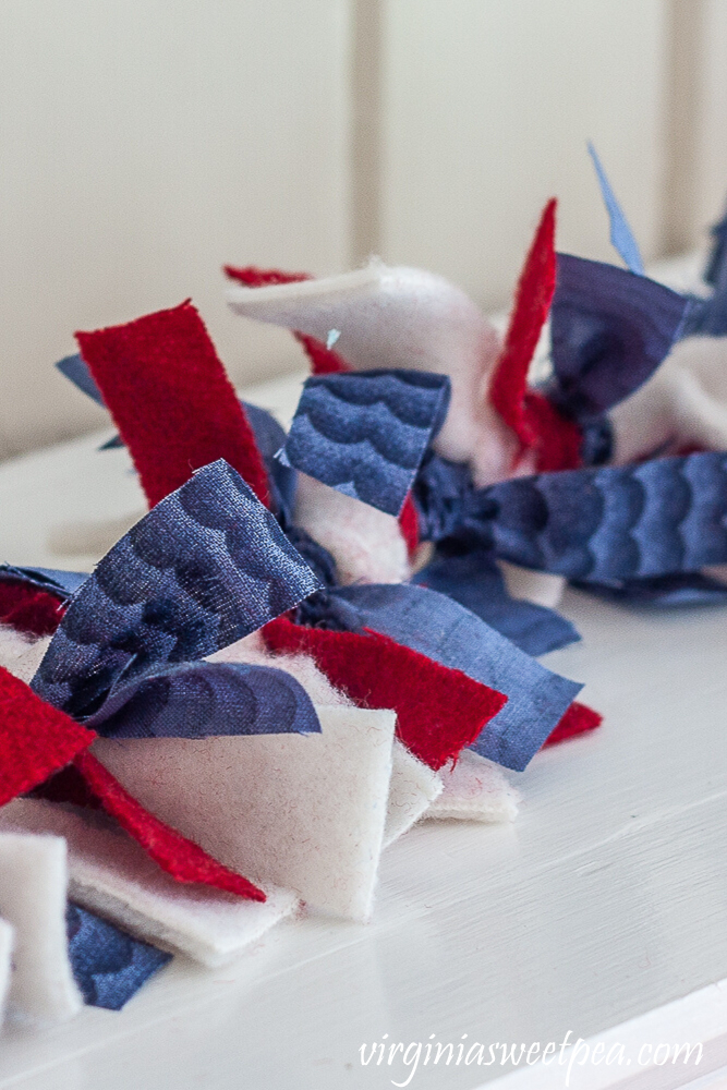 Garland made with strips of red, white, and blue fabric to decorate a mantel patriotically.