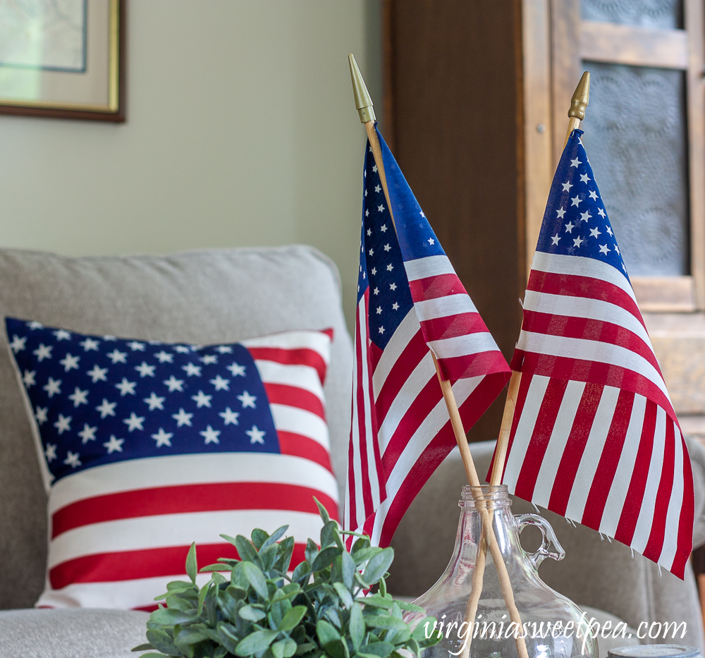 American flags displayed in a clear glass vintage jug with an American flag pillow