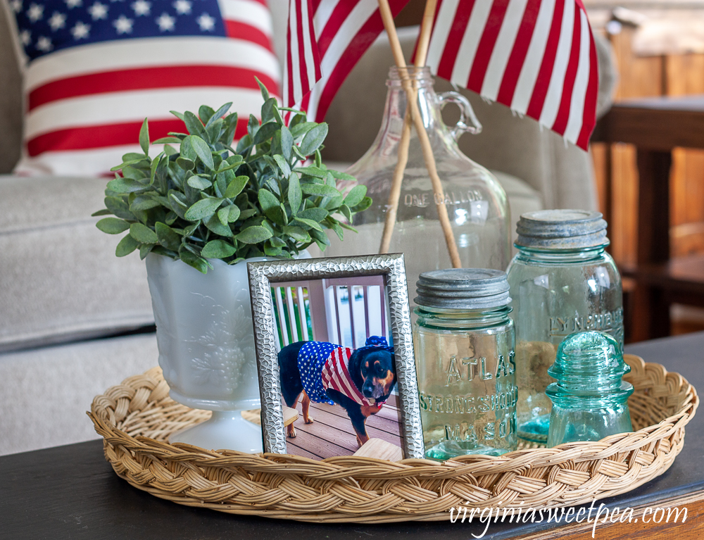 Patriotic Vignete with vintage Mason jars, vintage clear glass jug holding flags, and white milk glass compote with a faux plant