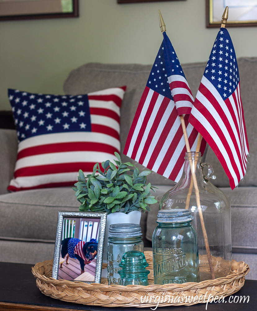 Patriotic Vignette with vintage Mason jars, vintage clear glass jug holding flags, and white milk glass compote with a faux plant and an American flag pillow in the background