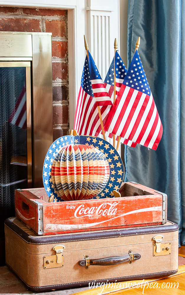 Patriotic Display with vintage suitcase, Coca-Cola crate, American flags, and a vintage red, white, and blue hat.