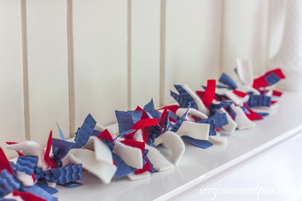 Rag garland made with red, white, and blue fabric strips, used on a mantel.