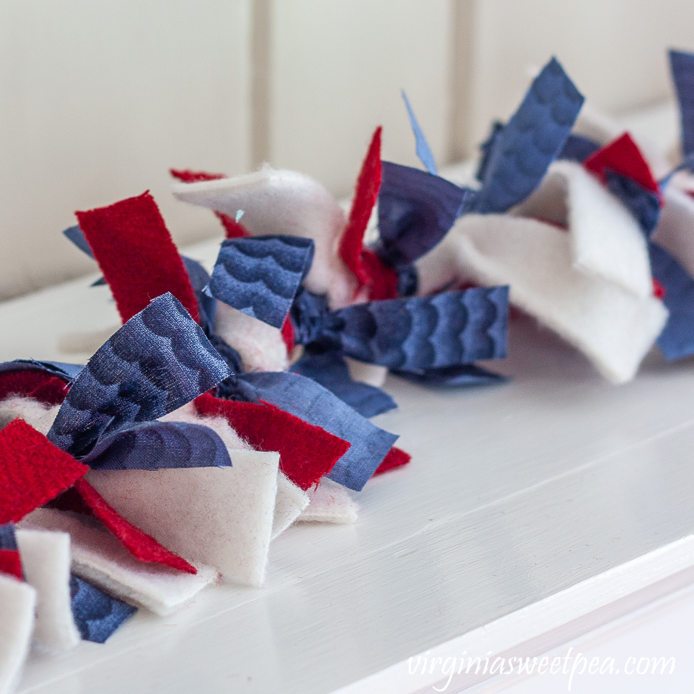 Rag garland made with blue quilting fabric, red wool, and white fleece