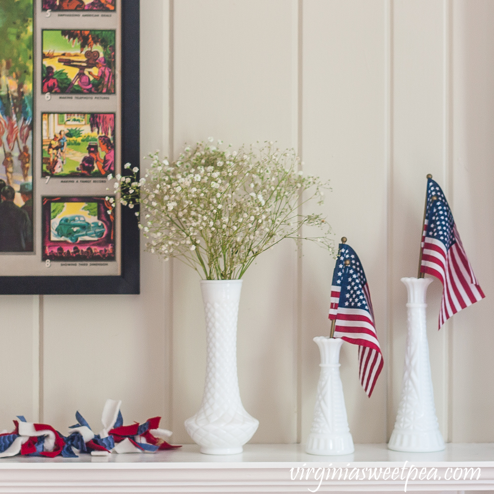 Milk glass vases with American flags and Baby's Breath on a mantel decorated patriotically.