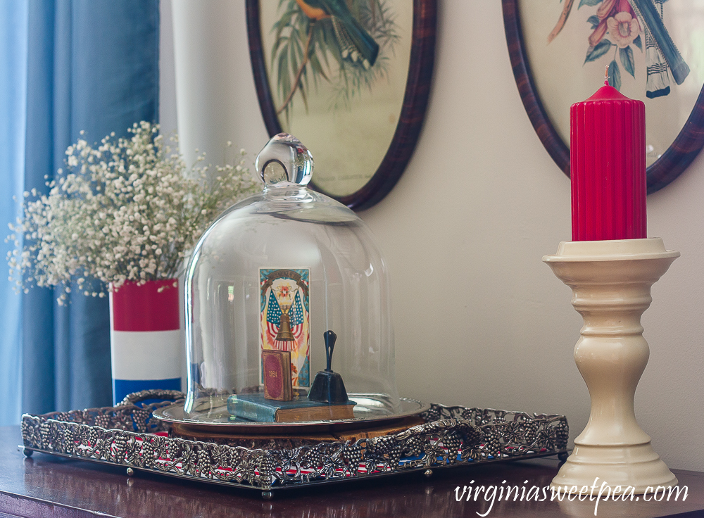 Patriotic Vignette with a red, white and blue striped vase with Baby's Breath and a cloche with a Liberty Bell postcard, 1924 mini book, a vintage bell, and a vintage bible with red candle on a cream colored candle holder.