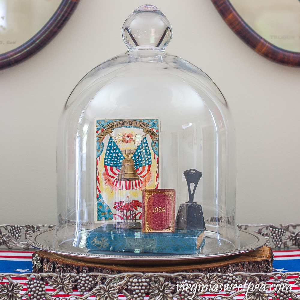 Cloche on a silver tray decorated with a Liberty Bell postcard, 1924 mini book, a vintage bell, and a vintage bible.