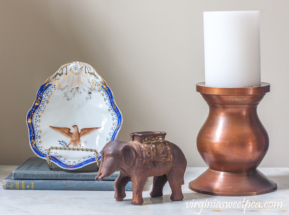 Vignette with an eagle dish, elephant, vintage books, and a copper candle holder with a white candle.