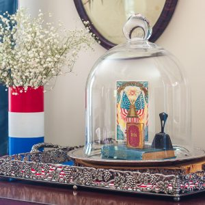Patriotic Vignette with a red, white and blue striped vase with Baby's Breath and a cloche with a Liberty Bell postcard, 1924 mini book, a vintage bell, and a vintage bible.