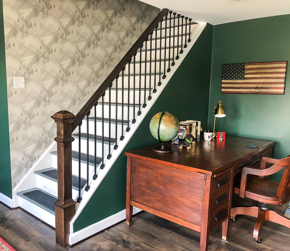 Wallpaper with a mountain and forest theme in a stairwell