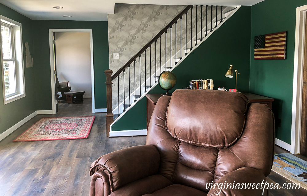 Wallpapered stairwell leading to a basement in a lake house