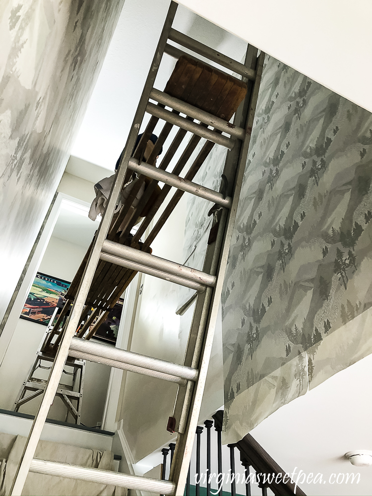 Installing wallpaper with a mountain and forest theme in a stairwell