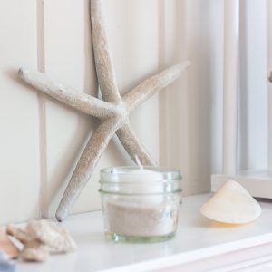 Starfish leaning against a mantel with a Ball jar filled with sand and a white votive candle.
