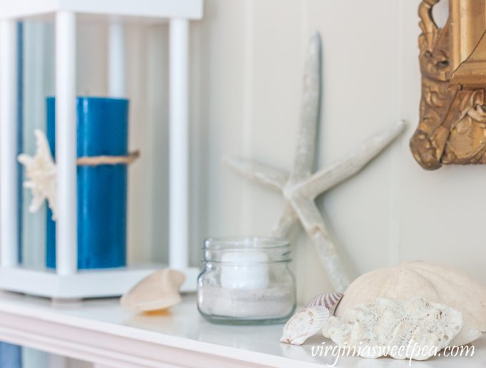 Summer mantel with starfish, shells, sand dollar, coral, and a lantern holding a blue candle.