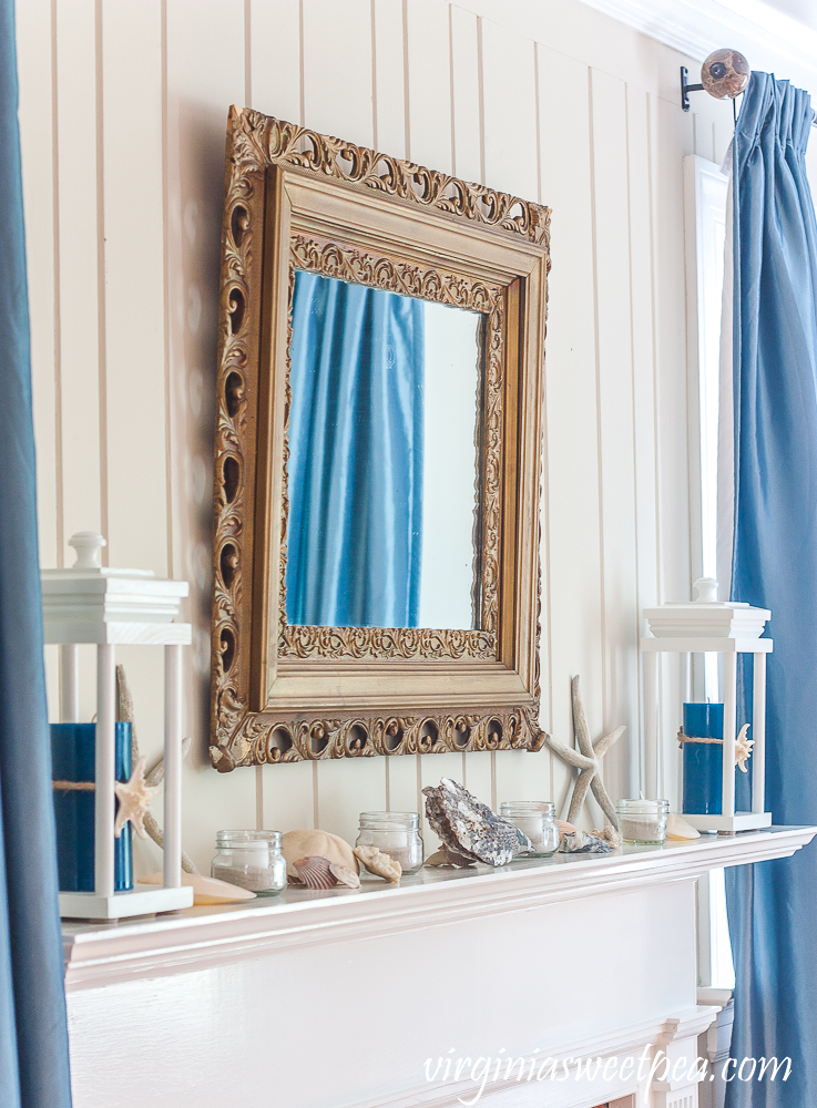 Gold mirror over a mantel decorated with a coastal theme.