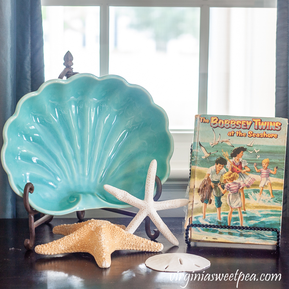 The Bobbsey Twins at the Seashore with a vintage shell shaped bowl, starfish, and sand dollar.
