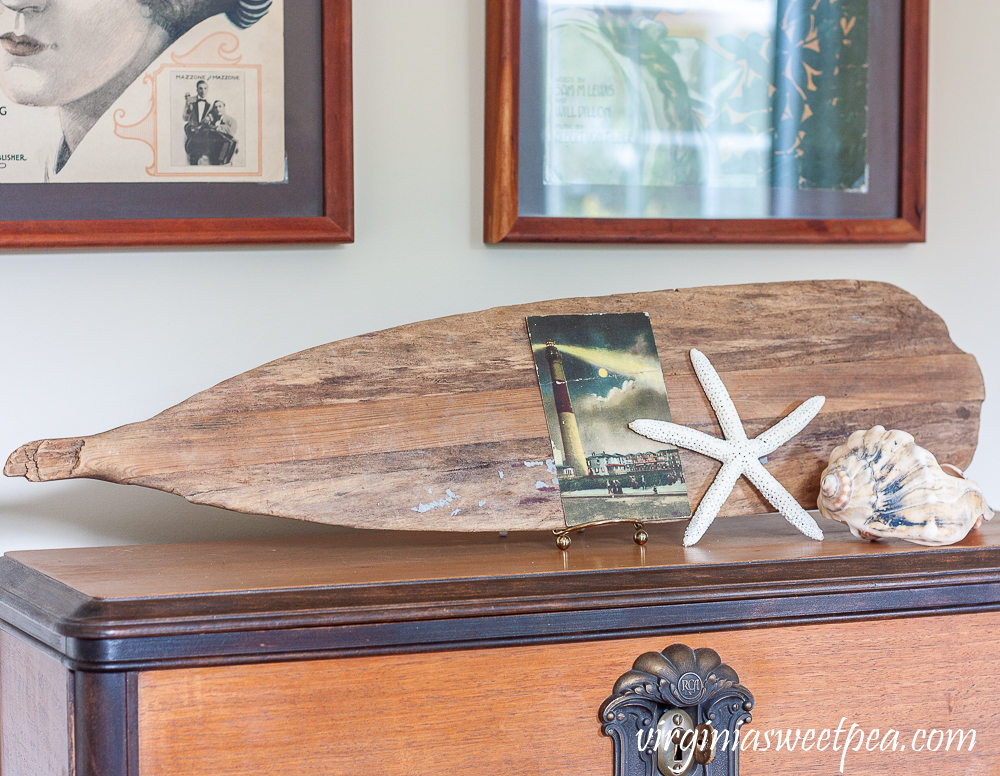 Old oar on display in a living room decorated for summer with a coastal theme.