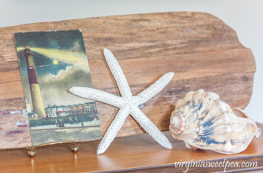 Vintage lighthouse postcard, starfish, and shell