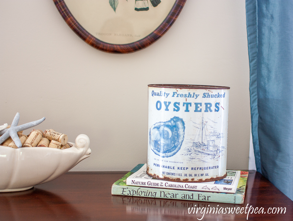 vintage oyster tin on top of two books with McCoy planter filled with wine corks and starfish