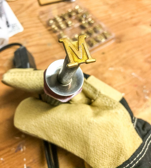 Attaching the letter M to a wood burning tool kit.