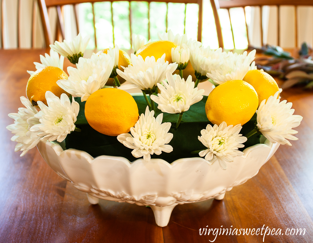 Lemons and flowers on skewers arranged in white milk glass Indiana fruit bowl