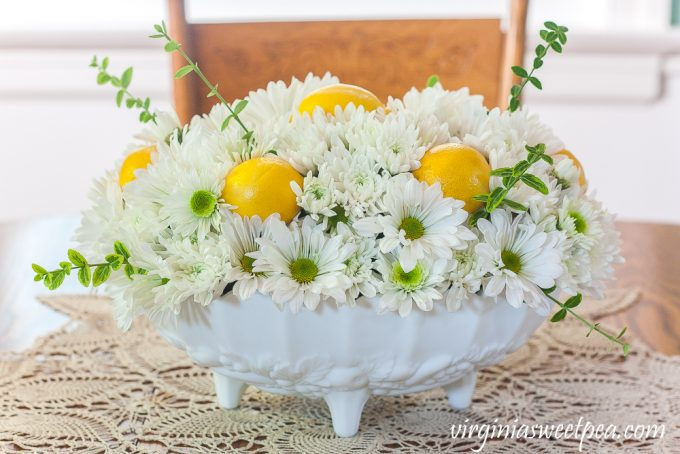Flower arrangement with Chrysanthemums, and Lemon in a white Indiana milk glass footed fruit bowl.