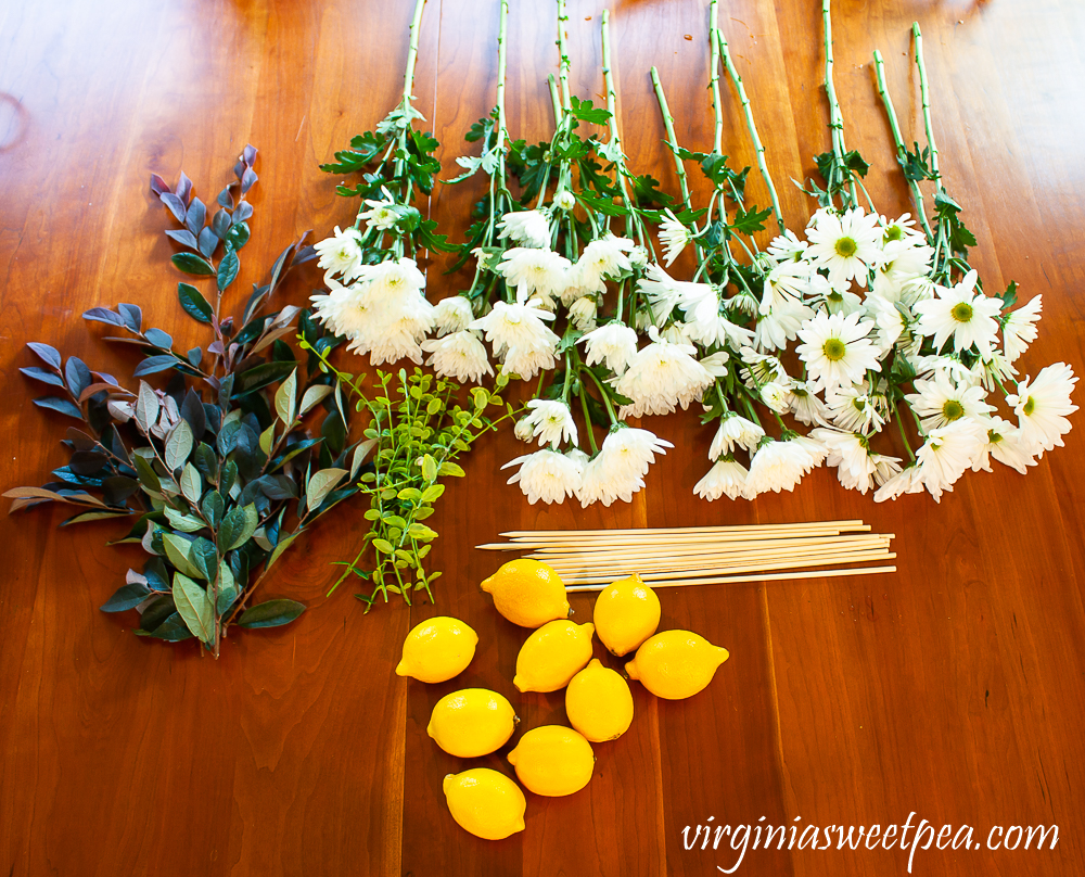 Flowers and fruit cut and prepped for making a flower arrangement